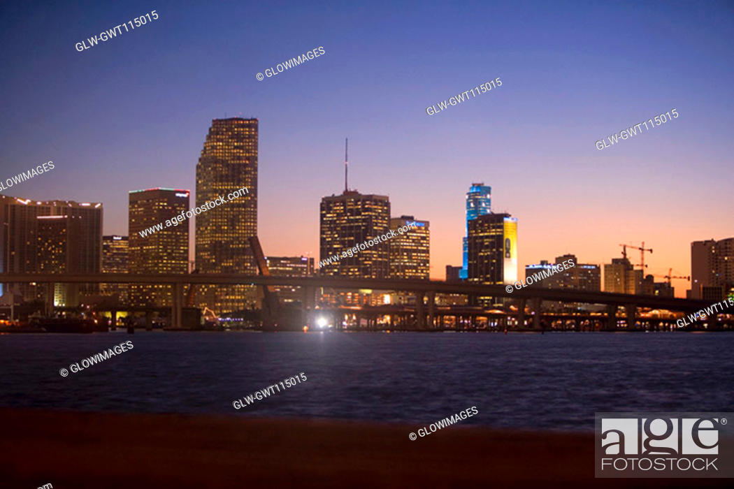 Stock Photo: Buildings at the waterfront lit up at dusk, Miami, Florida, USA.