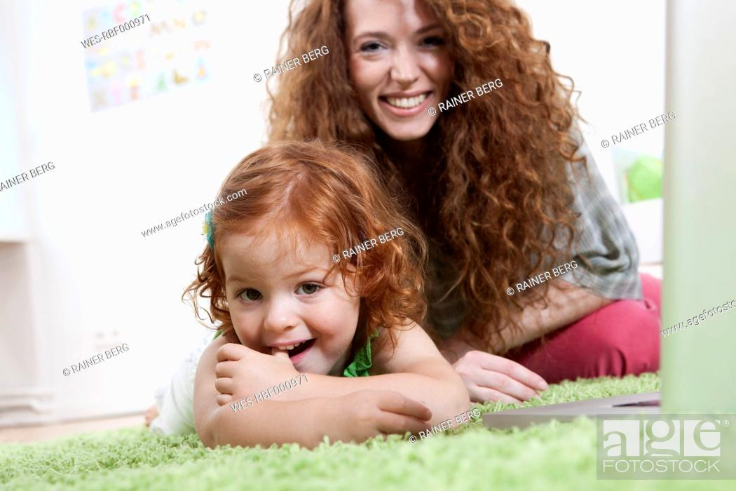 Stock Photo: Germany, Berlin, Mother and daughter relaxing on floor.