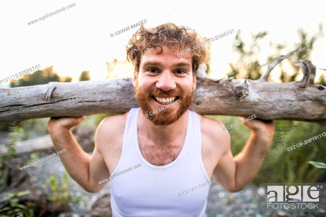 Stock Photo: portrait of man balancing log on shoulders during an outdoor workout.