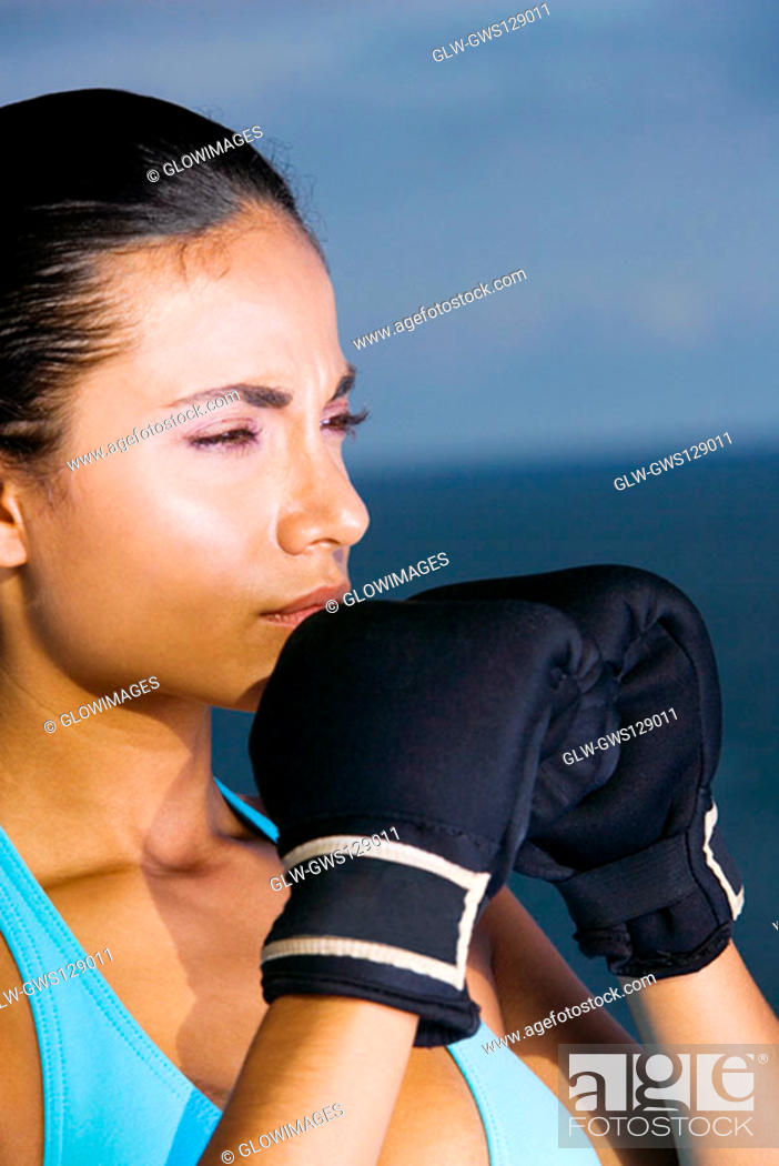 Stock Photo: Close-up of a young woman wearing boxing gloves.