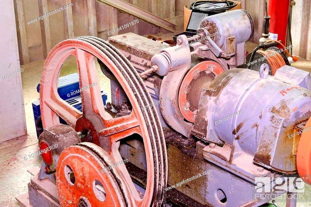 Stock Photo: Part of industrial lift. Pulley wheel and engine in engine room. Reconstruction of industrial lift.