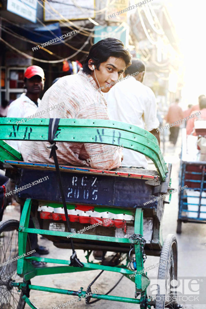 Stock Photo: Rear view of a young man sitting in a rickshaw and listening to an MP3 player.