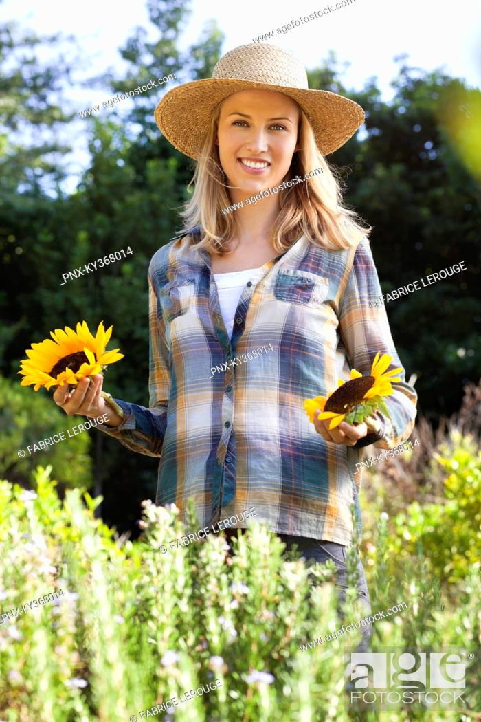 Stock Photo: Portrait of a young woman holding sunflowers in a field.