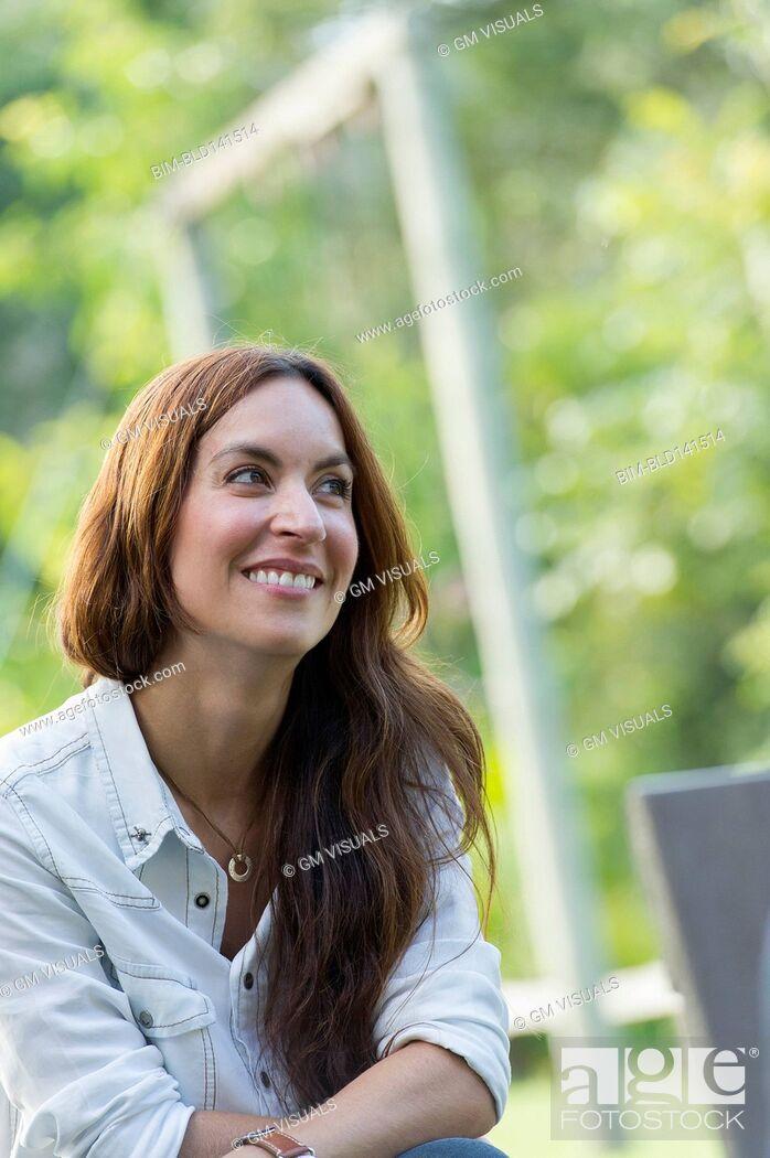 Stock Photo: Hispanic woman smiling outdoors.
