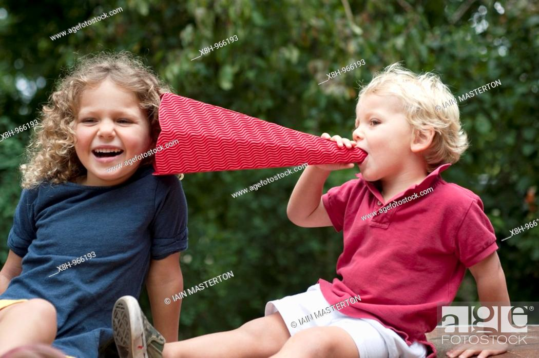Stock Photo: Young children using a toy cardboard megaphone to talk to each other while having fun.