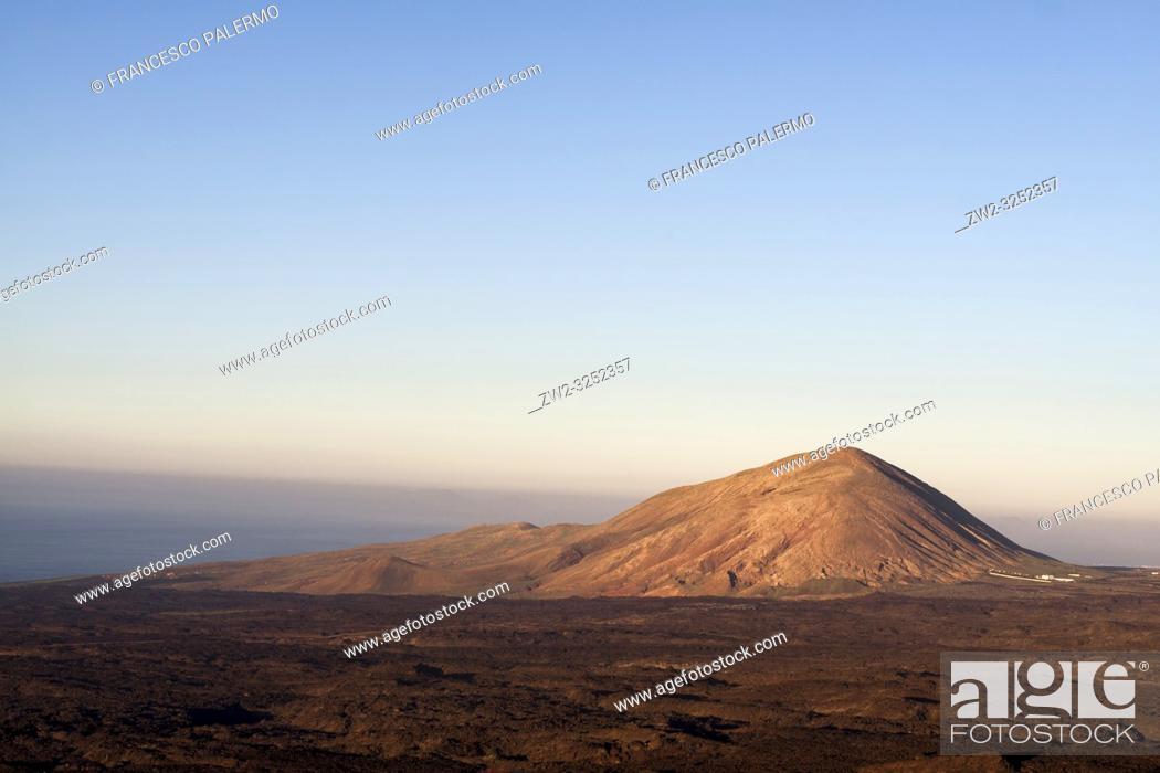 Stock Photo: Warm sunset illuminates the volcano. Timanfaya, Lanzarote. Spain.