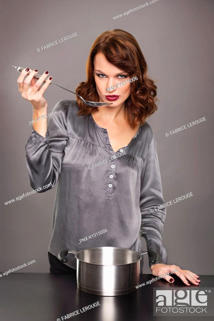 Stock Photo: Young woman tasting food.