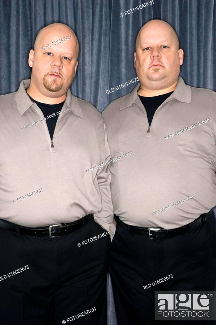 Stock Photo: Bald identical twin mid adult men standing together looking at viewer.