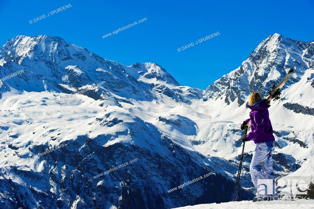 Stock Photo: A skier looks out over a stunning winter snowy mountains.