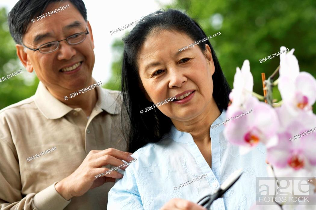 Stock Photo: Senior Asian couple pruning flowers.