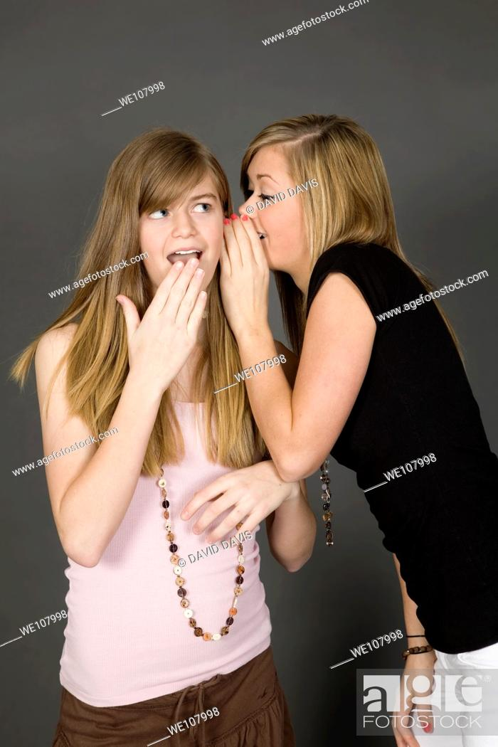 Stock Photo: Teenage girls telling secrets posed in front of a gray background.
