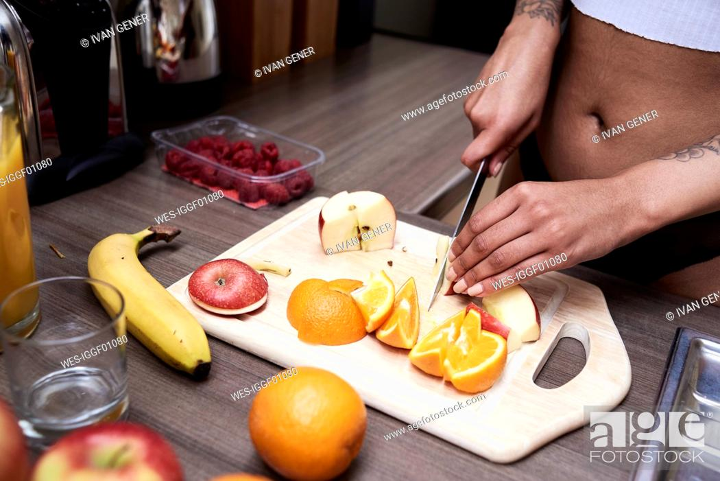 Stock Photo: Close-up of young woman cutting fruit in kitchen.