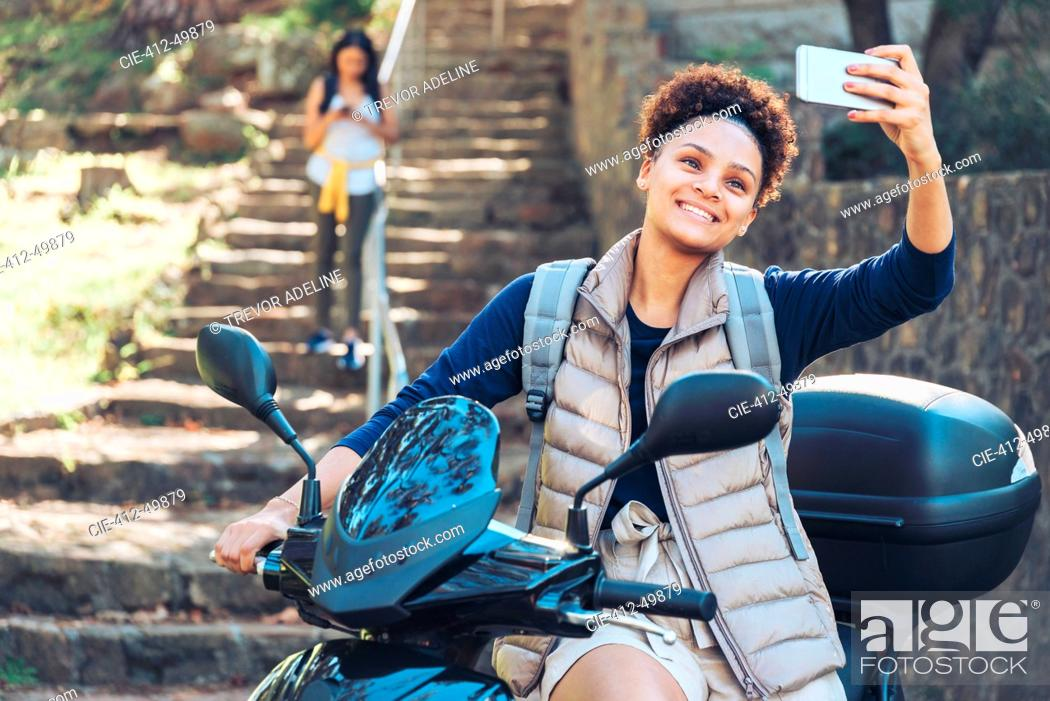 Photo de stock: Young woman taking selfie with camera phone on motor scooter.