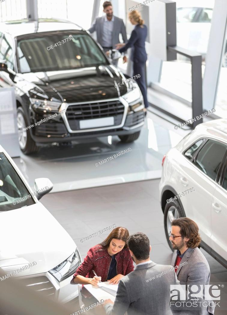Stock Photo: Car sales people and customers in car dealership showroom.