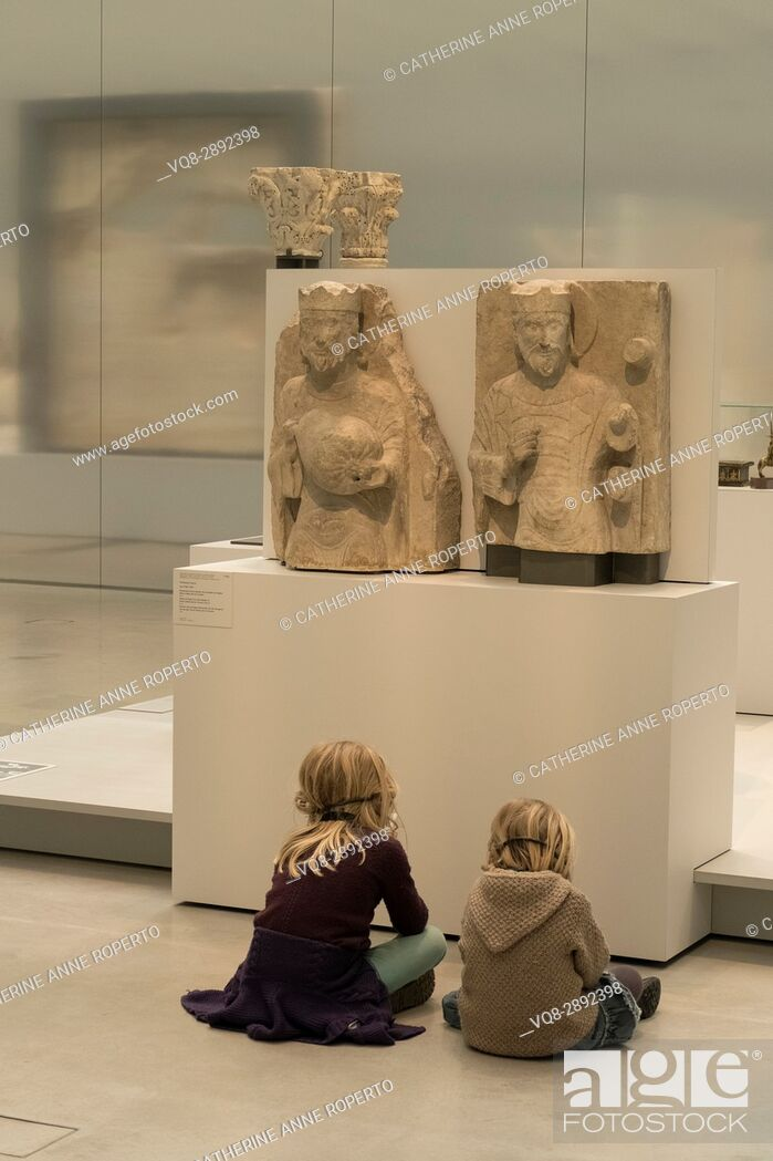 Imagen: Two light haired children sat cross legged in front of two light stone crowned figure carvings, listening to historical commentaries, Louvre-Lens Museum.