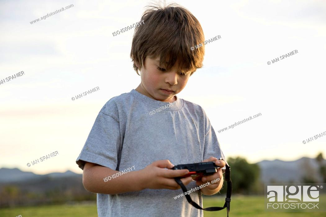 Stock Photo: Boy looking at digital camera in park.