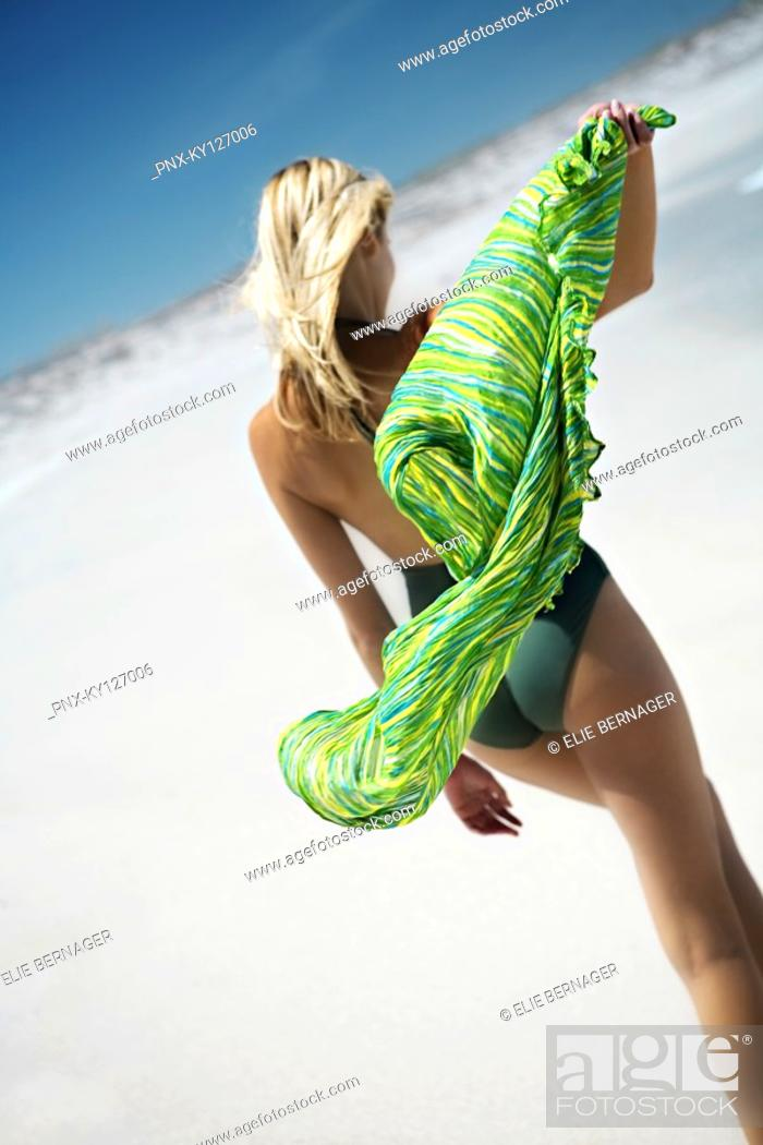 Stock Photo: Young woman in swimming costume, walking on the beach, rear view.