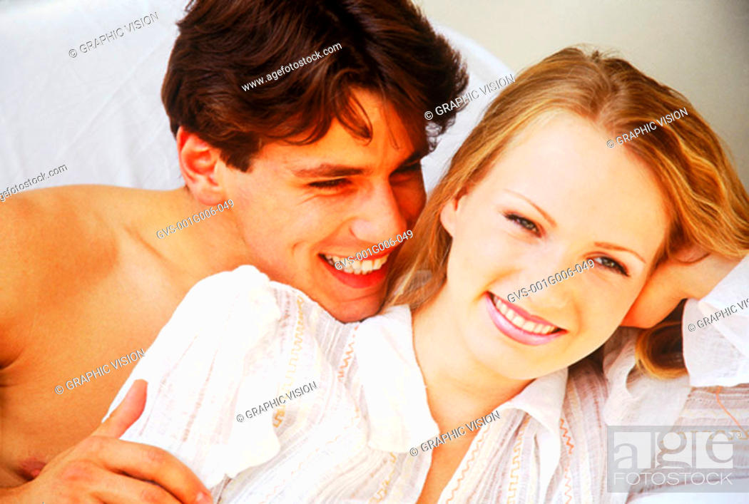 Stock Photo: Young couple lying together smiling.
