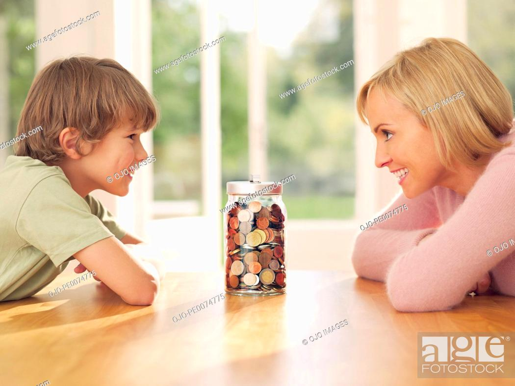 Stock Photo: Mother and son looking at jar full of coins.
