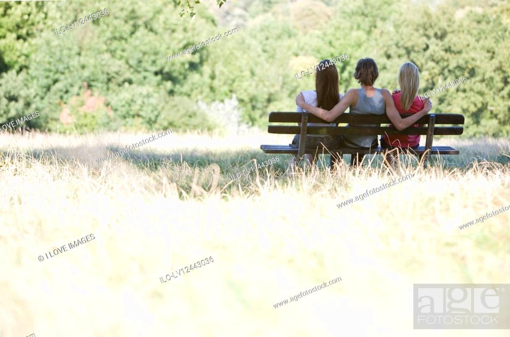 Stock Photo: Three young people sitting on a bench in a park.