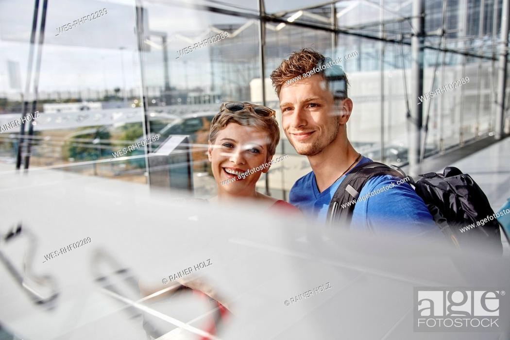 Stock Photo: Portrait of smiling couple at the airport looking out of window.
