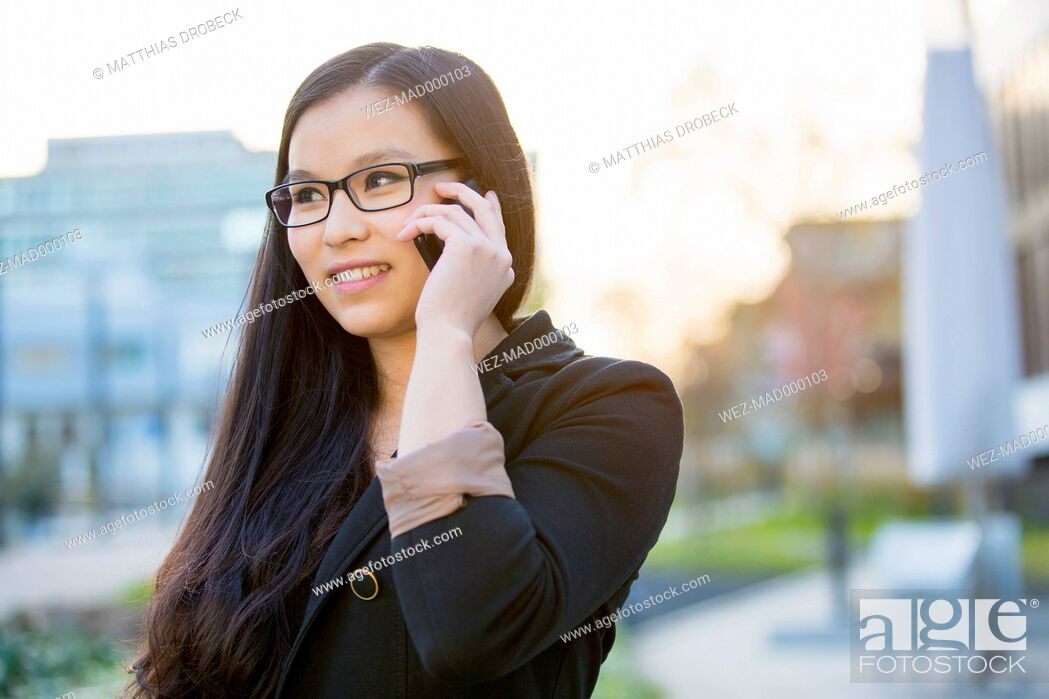 Stock Photo: Portrait of young businesswoman telephoning with smartphone.