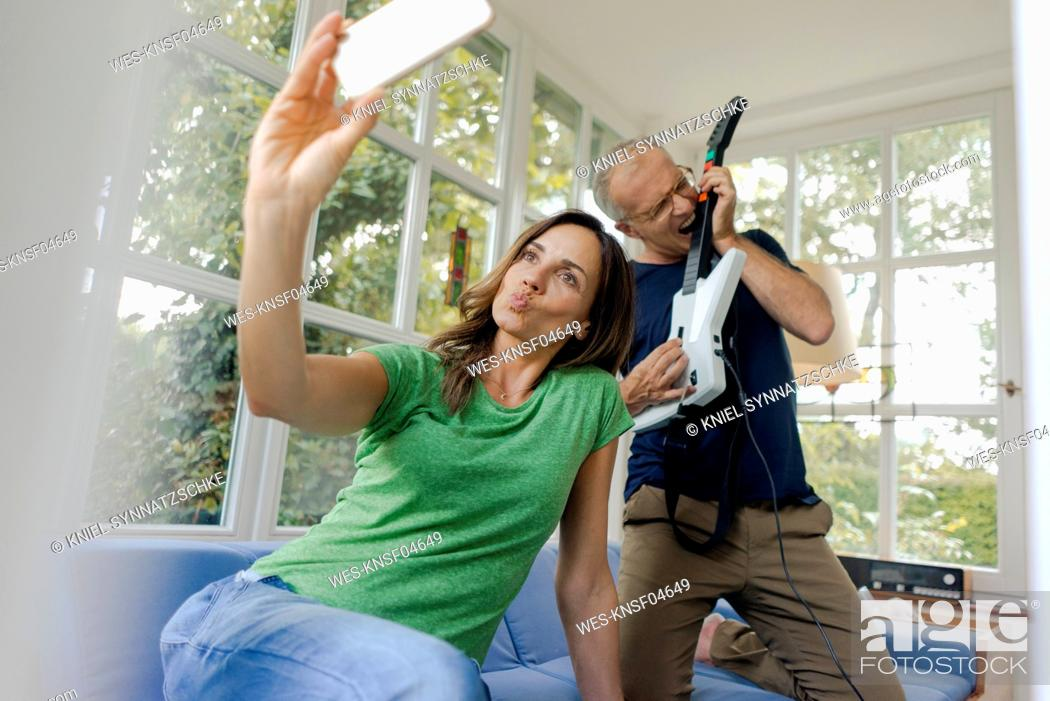 Imagen: Mature woman taking a selfie at home with man playing toy electric guitar.