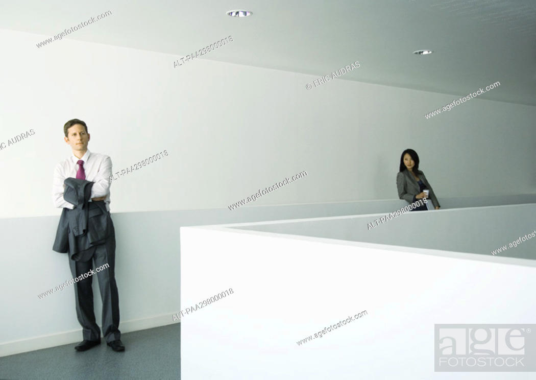 Stock Photo: Businessman and businesswoman standing apart in office building.