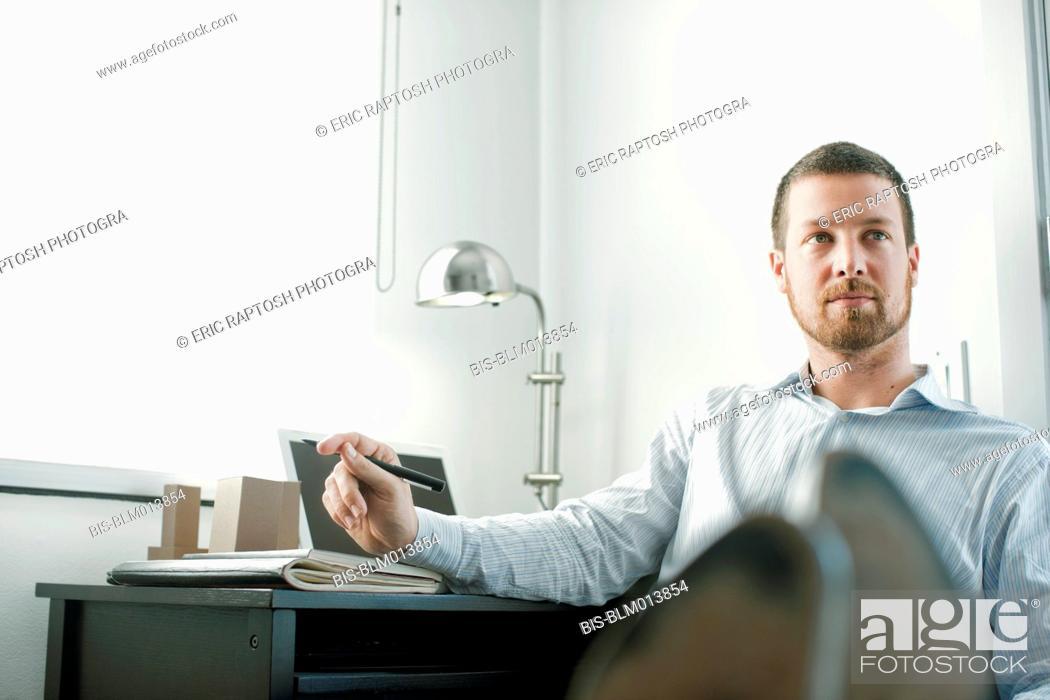 Imagen: Caucasian businessman sitting at desk with feet up.