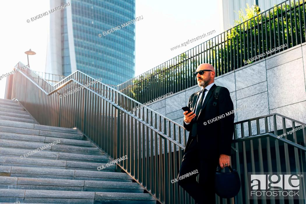 Imagen: Mature businessman standing on steps, using smartphone, low angle view.