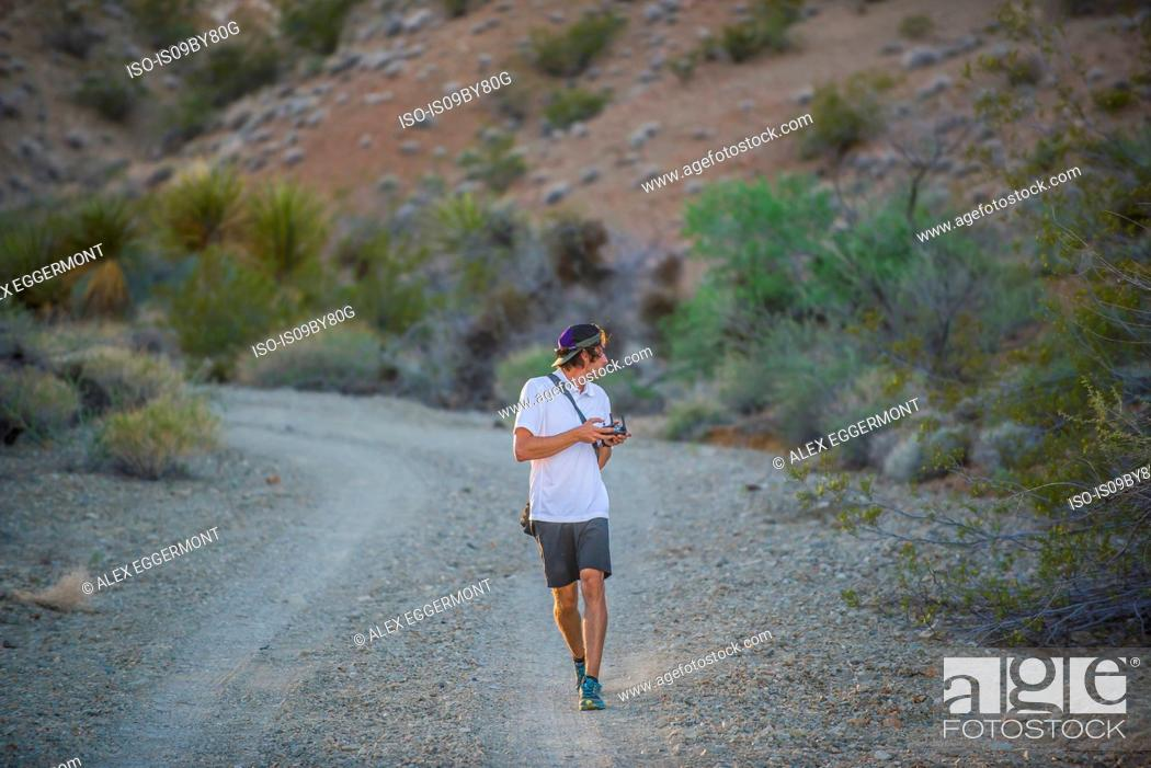 Stock Photo: Man walking along dirt track operating drone (unmanned aerial vehicle).