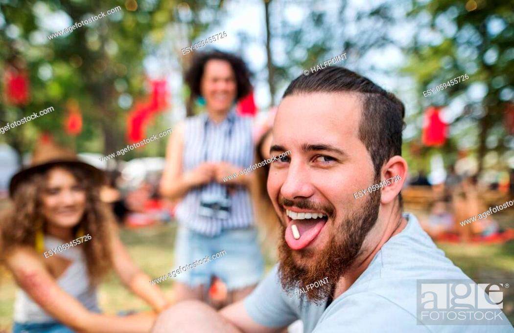 Stock Photo: Group of young friends sitting on ground at summer festival, drug dealing concept.