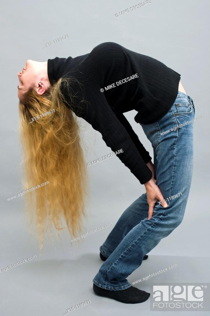 Stock Photo: An attractive American woman in blue jeans and a black sweater with beautiful long, flowing blond hair, bends over backwards.