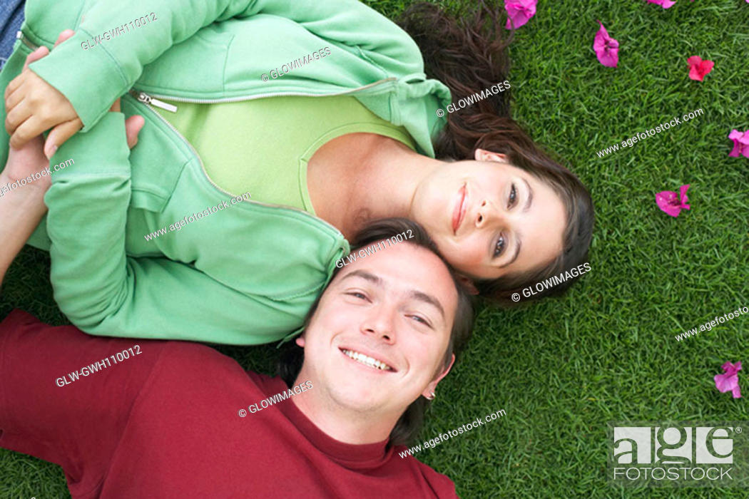 Stock Photo: High angle view of a mid adult man and a young woman lying on the grass and smiling.