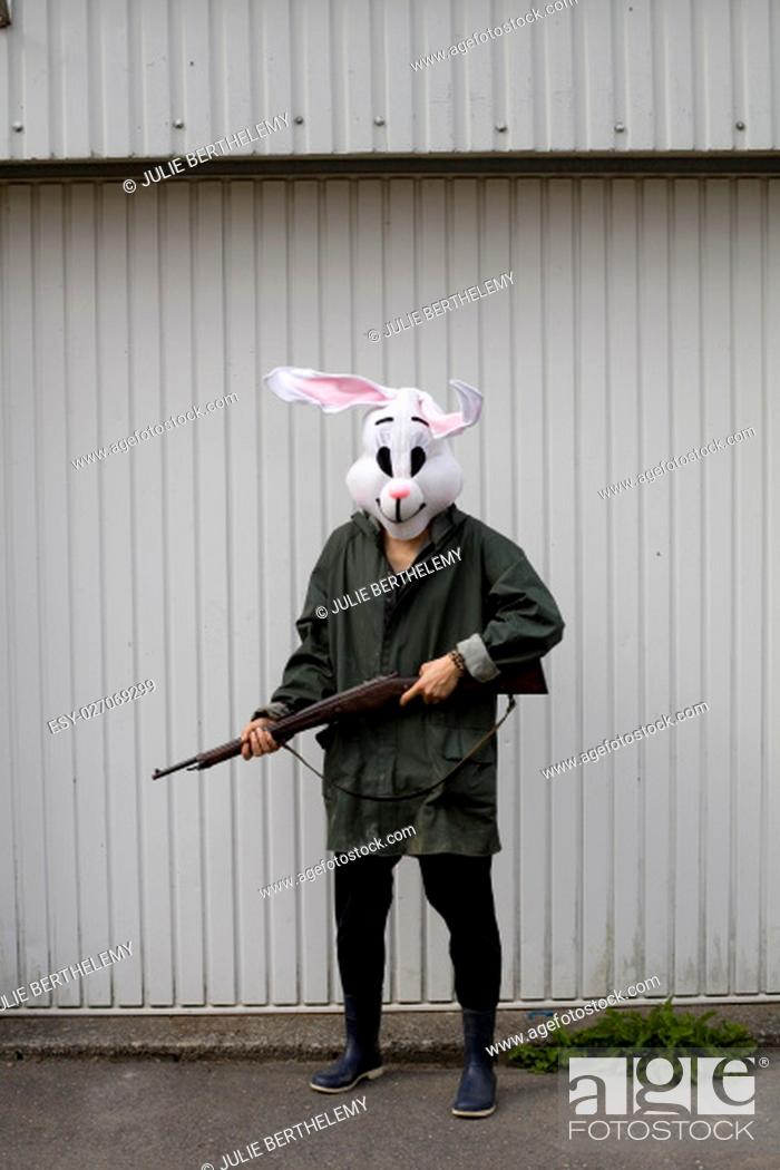 Stock Photo: .woman wearing a rabbit mask hunting with shotgun in a forest.