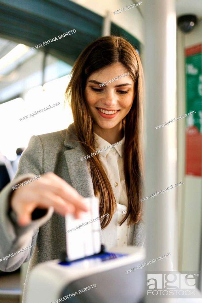 Stock Photo: Portrait of smiling young woman validating ticket in tramway.