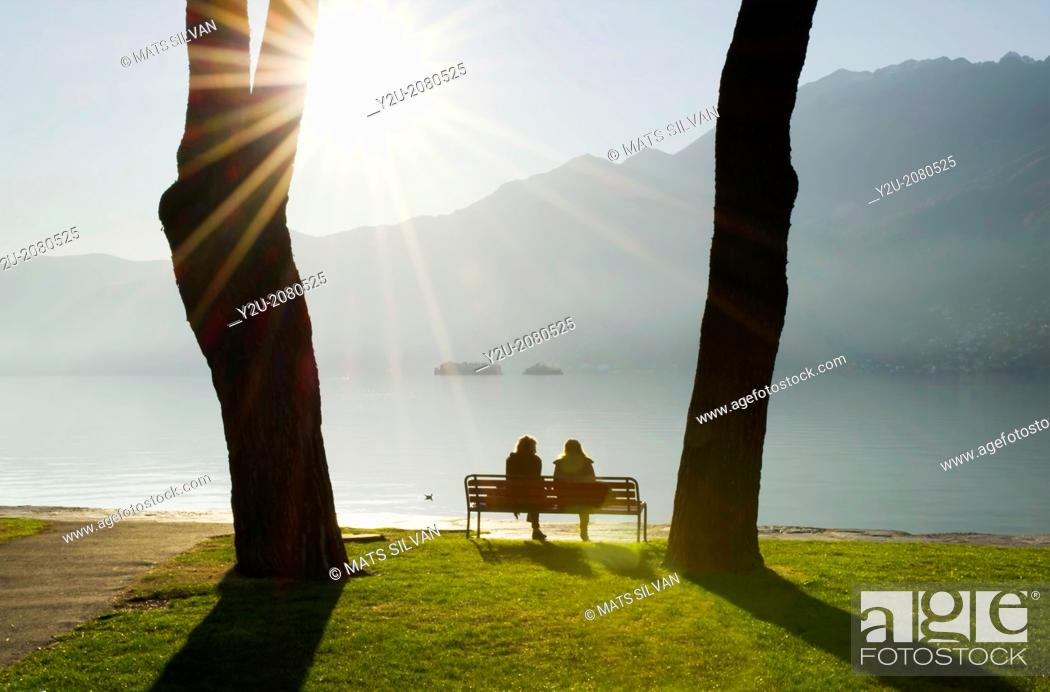 Stock Photo: Couple sitting on a bench on the lakefront maggiore with brissago islands and mountain with sunbeam on a misty lake in ascona ticino switzerland.