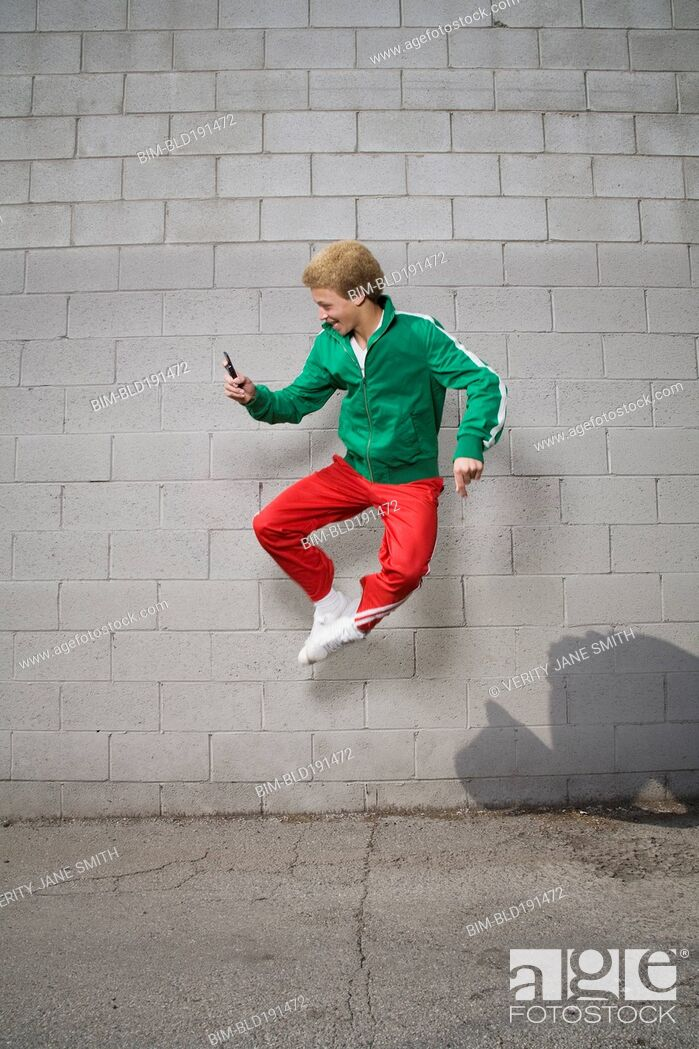 Stock Photo: Mixed race boy jumping in mid-air using cell phone.