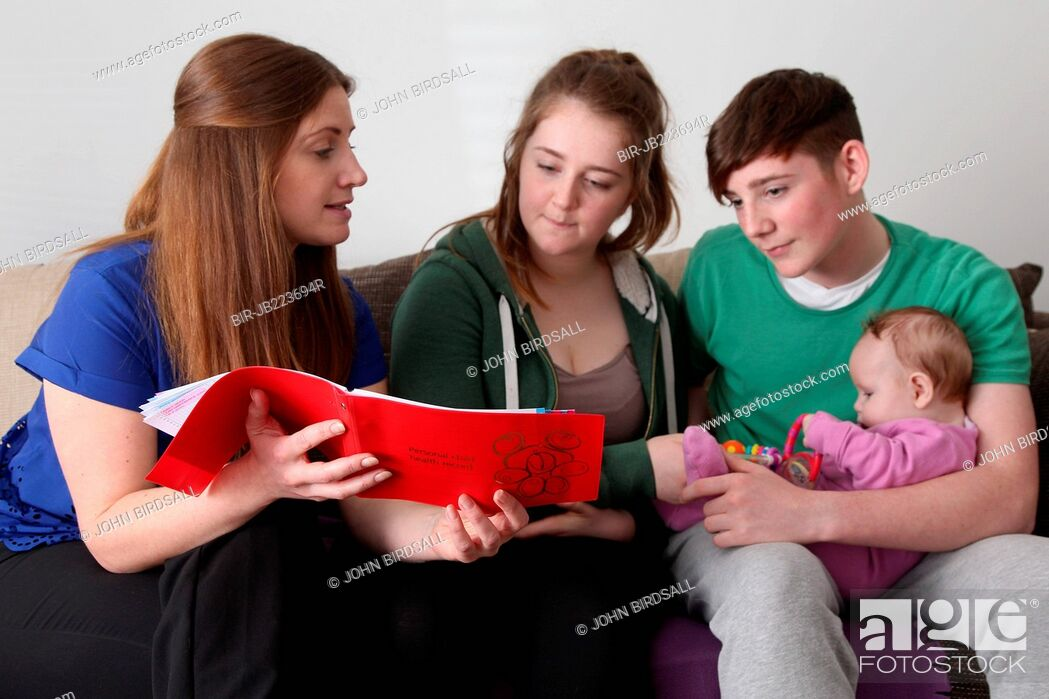 Stock Photo: Health visitor visiting teenage couple with baby.