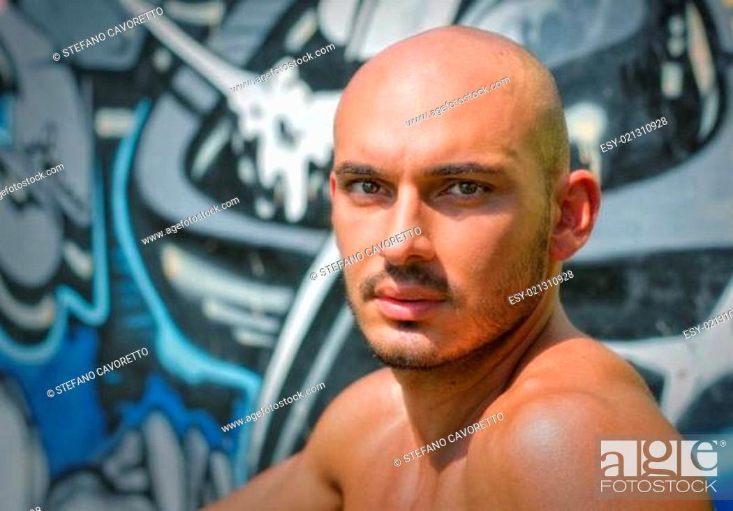 Stock Photo: Headshot of bald young man shirtless outdoors.
