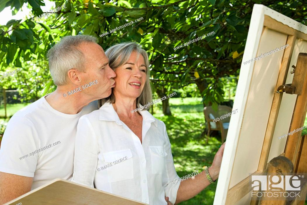 Stock Photo: Mature couple, woman painting at easel.