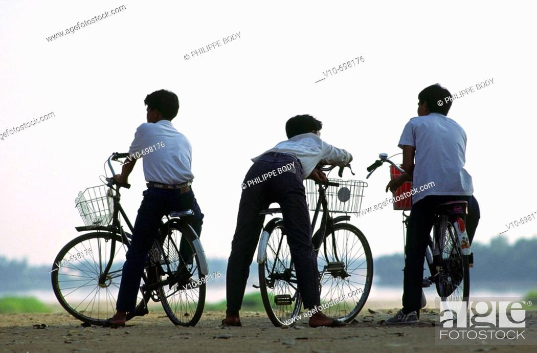 Stock Photo: Teenagers on their bicycle watching the Mekong river, Vientiane, Laos.