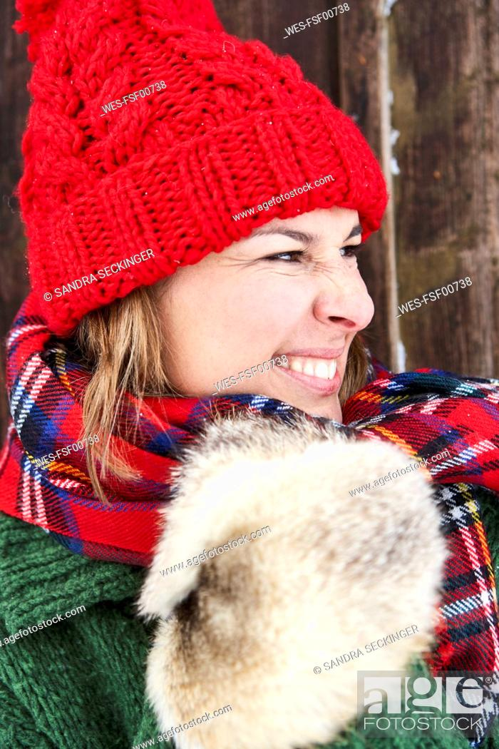 Stock Photo: Portrait of woman wearing red bobble hat and fur gloves in winter.