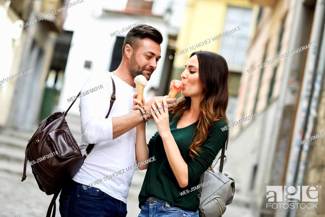 Stock Photo: Tourist couple sharing ice cream cones in the city.