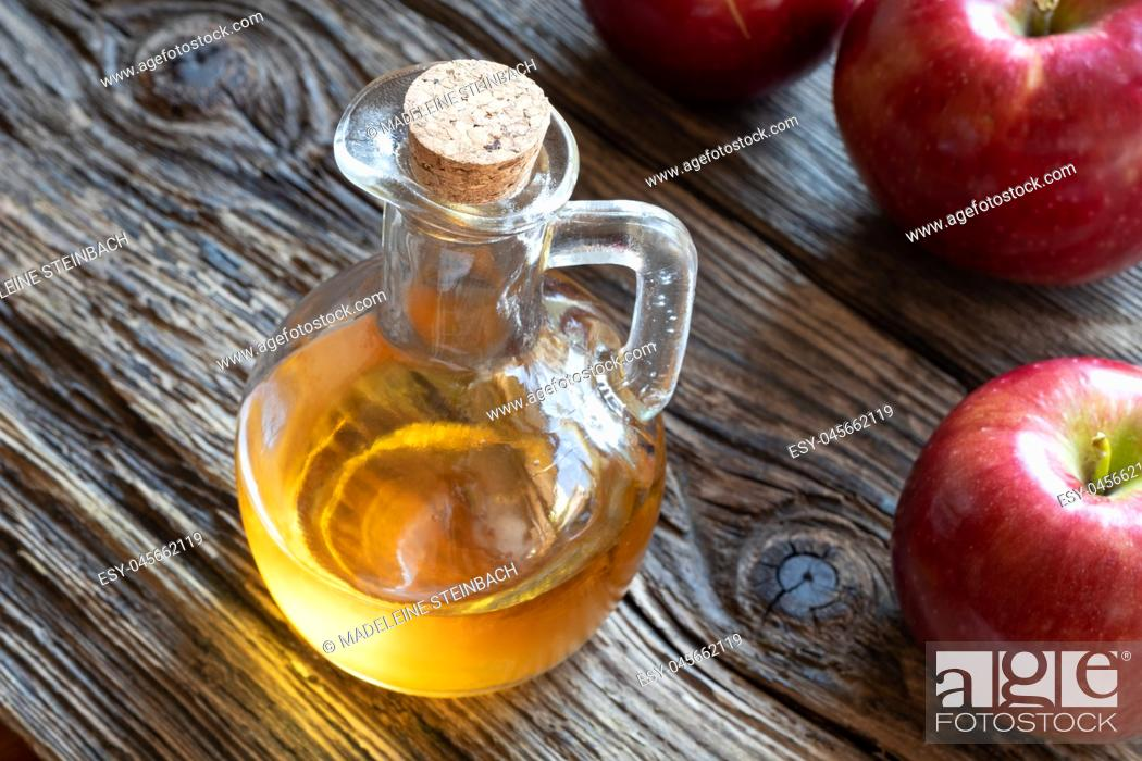 Stock Photo: A bottle of apple cider vinegar on a rustic background.