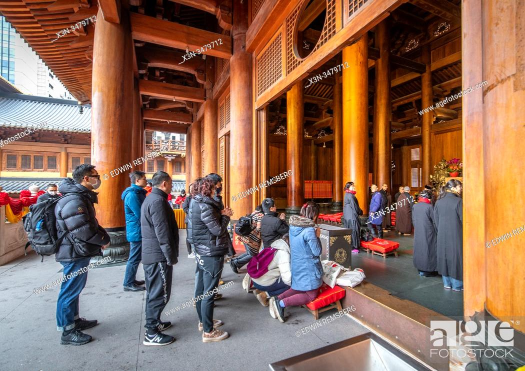 Stock Photo: People praying at an altar in the Jing'an Temple , Shanghai, China.