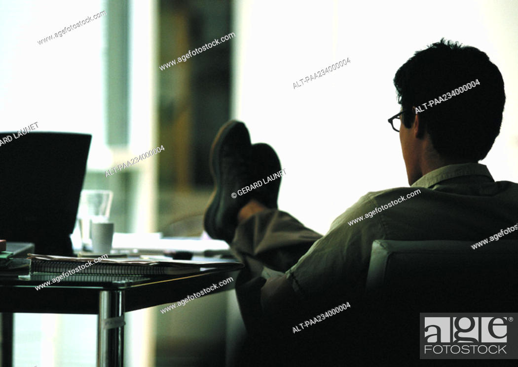 Stock Photo: Man sitting in chair with feet on table, rear view.