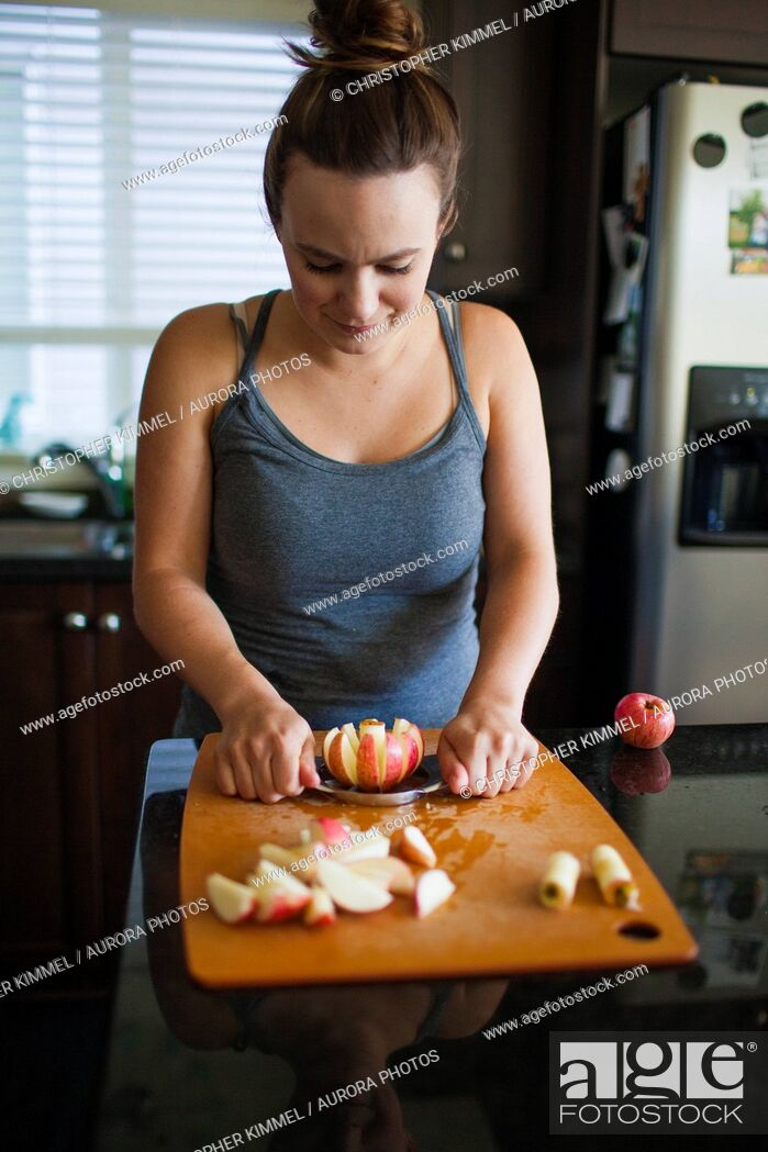 Imagen: Front waist up view of woman slicing apple with apple slicer for apple sauce.