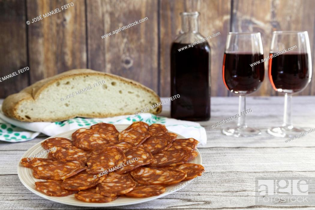 Stock Photo: typical Spanish chorizo sausage sliced on a plate, bread, red wine rustic bottle and two red wine glasses on wooden table and wooden background.