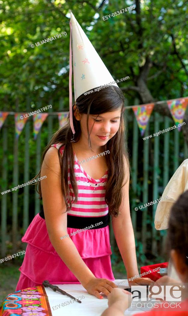 Stock Photo: little preteen pretty girl with thick brown hair in birthday cone hat close up party photo on summer green ourdoor background.